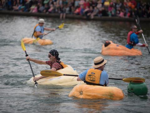 오리건주 투알라틴의 웨스트 코스트 자이언트 펌킨 레가타에서 호박을 타고 노를 젓는 참가자들